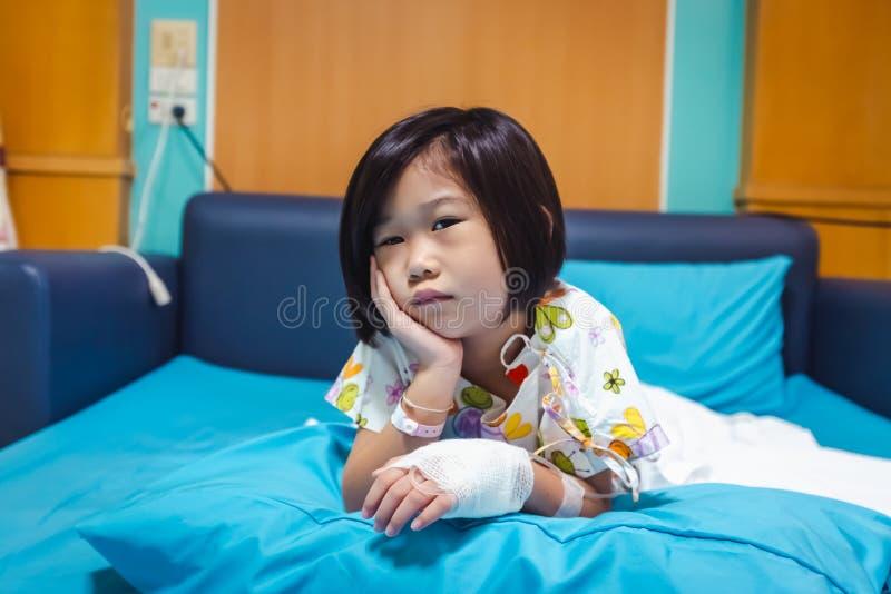 病症亚裔孩子在有盐iv滴水的医院在手边承认了 医疗保健故事 免版税库存图片