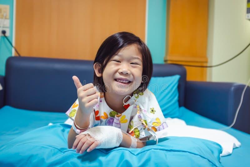 病症亚裔孩子在有盐iv滴水的医院在手边承认了 o 免版税图库摄影
