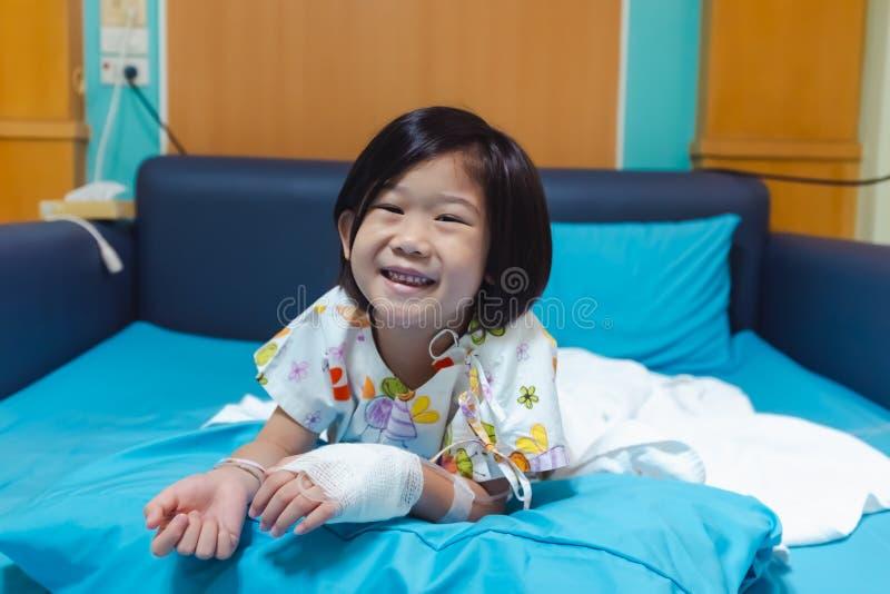 病症亚裔孩子在有盐iv滴水的医院在手边承认了 o 库存照片