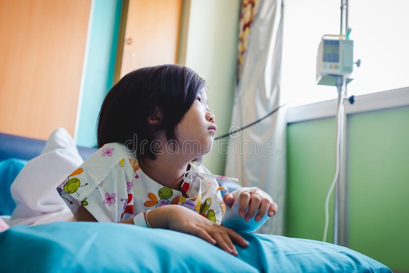 病症亚裔孩子在有盐iv滴水的医院在手边承认了 o 免版税库存照片