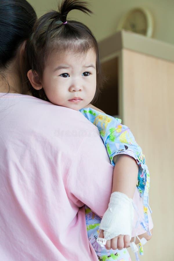 病症孩子在医院,盐静脉注射(iv)在手边亚洲人 库存图片