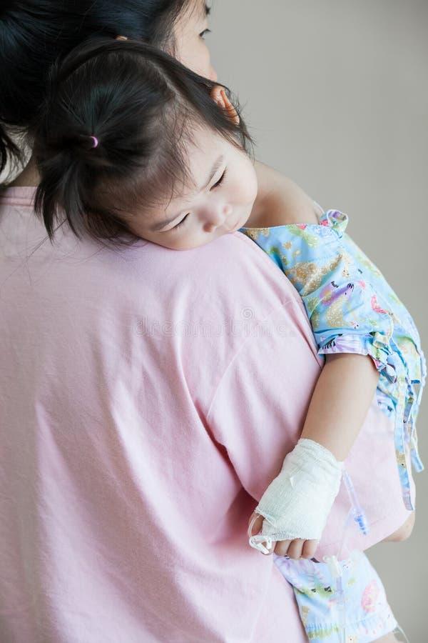 病症孩子在医院,盐静脉注射(iv)在手边亚洲人 免版税库存照片