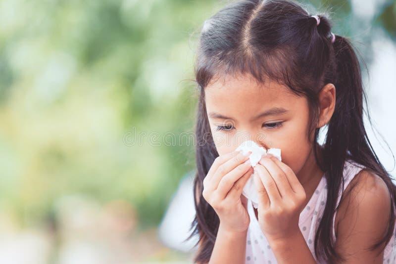 病的亚裔与组织的儿童女孩抹的和清洗的鼻子 免版税库存照片