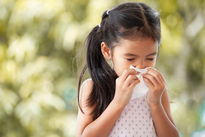 病的亚裔与组织的儿童女孩抹的和清洗的鼻子 免版税库存图片