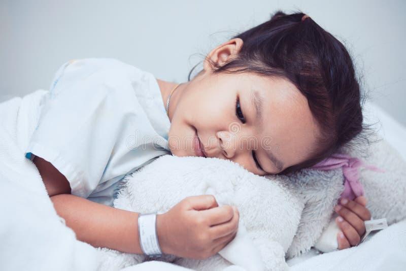 病的亚裔儿童女孩在床上在并且拥抱她的玩偶 图库摄影