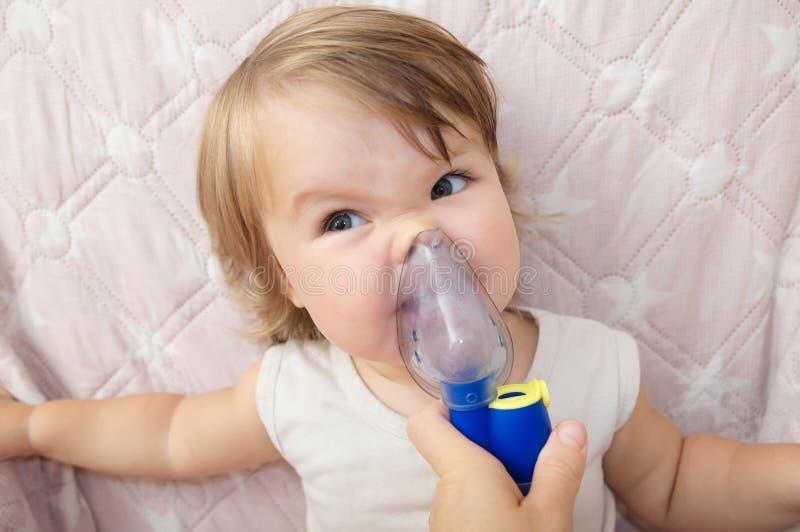 病的女婴和穿上` t要为孩子使用做吸入、呼吸做法由肺炎或咳嗽的雾化器面具 库存图片
