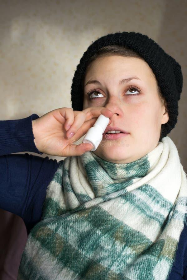 病的女孩喷洒从流鼻水的浪花入鼻通行证 库存照片
