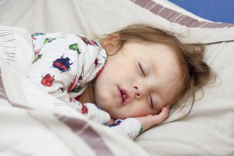 病的女孩在床上 库存图片