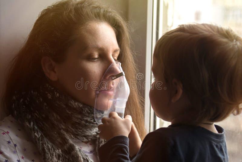 病的女孩在他的面孔做与面具的吸入 免版税库存图片