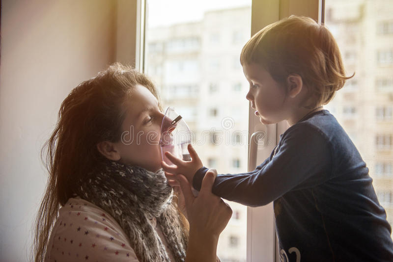 病的女孩在他的面孔做与面具的吸入 库存照片