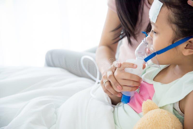 病的女孩坐与氧气面罩的床 免版税库存图片