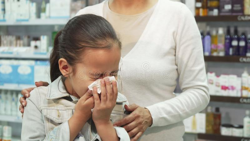 病的女孩打喷嚏并且抹她的鼻子与餐巾 图库摄影