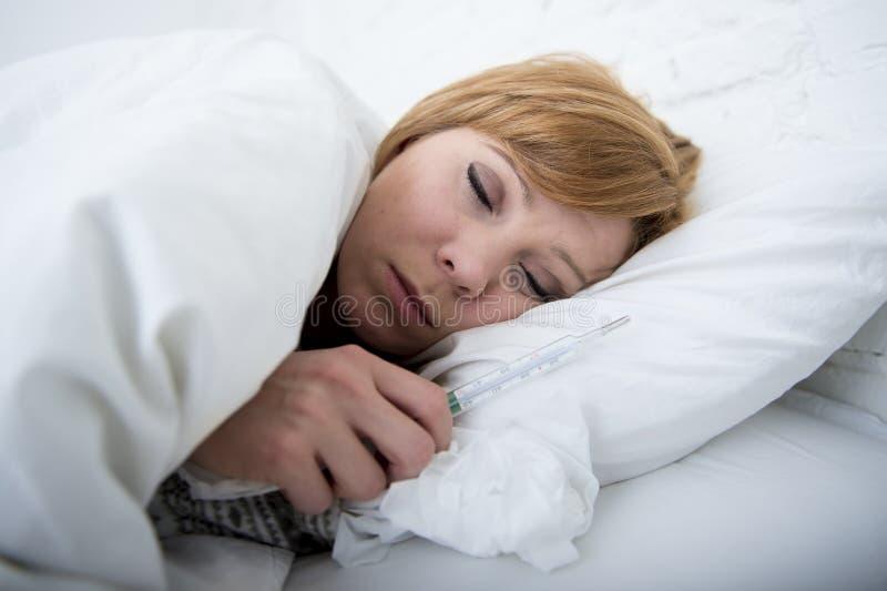 病的妇女在与温度计狂热微弱的痛苦冷的冬天流感病毒的床上 库存照片
