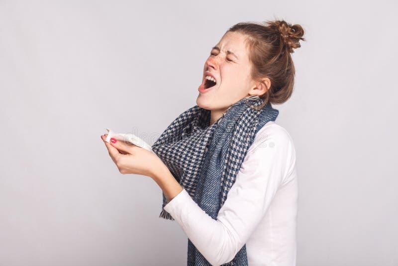 病的妇女拿着一张手帕并且打喷嚏 免版税库存照片