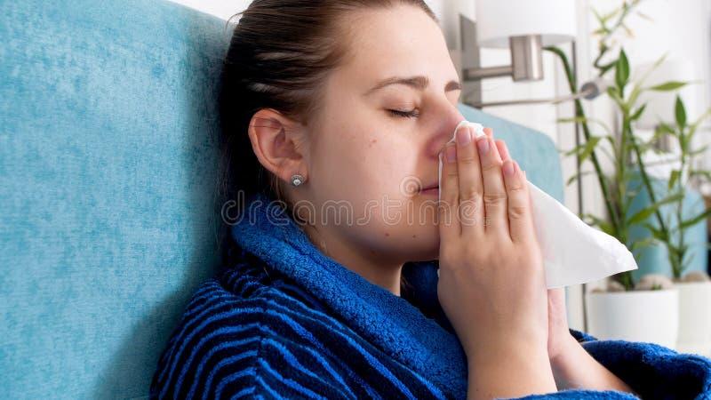 病的妇女画象捉住了冷在家休息在床和在纸手帕的吹的鼻子上 库存图片