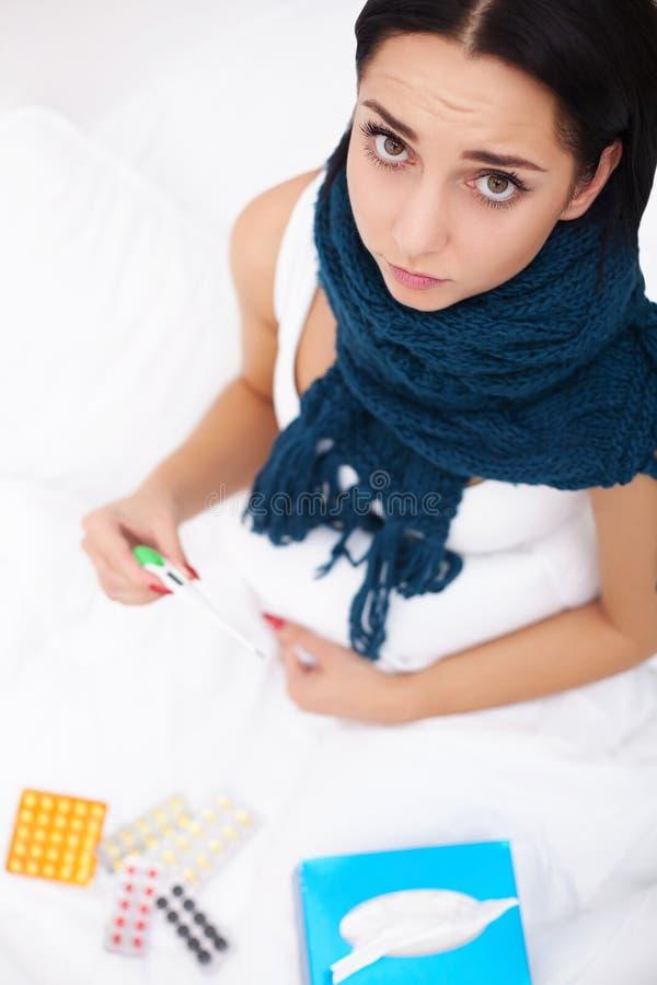病的妇女 流感 有冷说谎的女孩在举行a的毯子下 库存图片