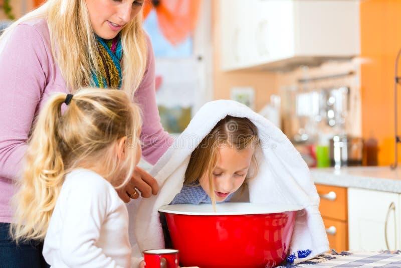病的孩子的母亲关心有蒸气浴的 免版税库存图片