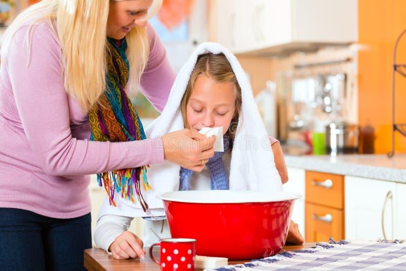 病的孩子的母亲关心有蒸气浴的 库存图片