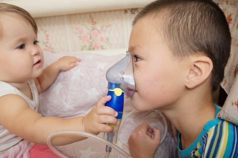 病的孩子-女婴和男孩用途吸入的雾化器面具,由肺炎的呼吸孩子的做法或咳嗽 库存图片