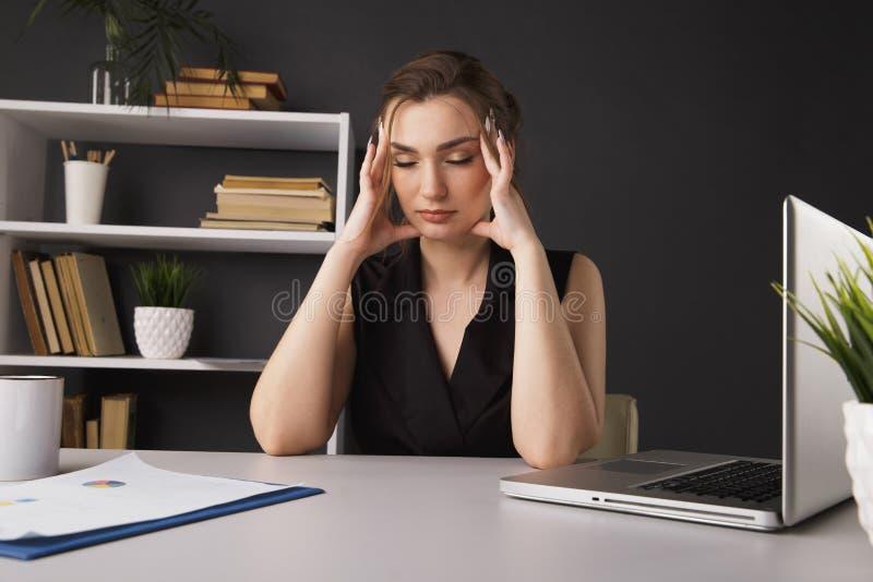 病的年轻女人以偏头痛在办公室 免版税库存照片