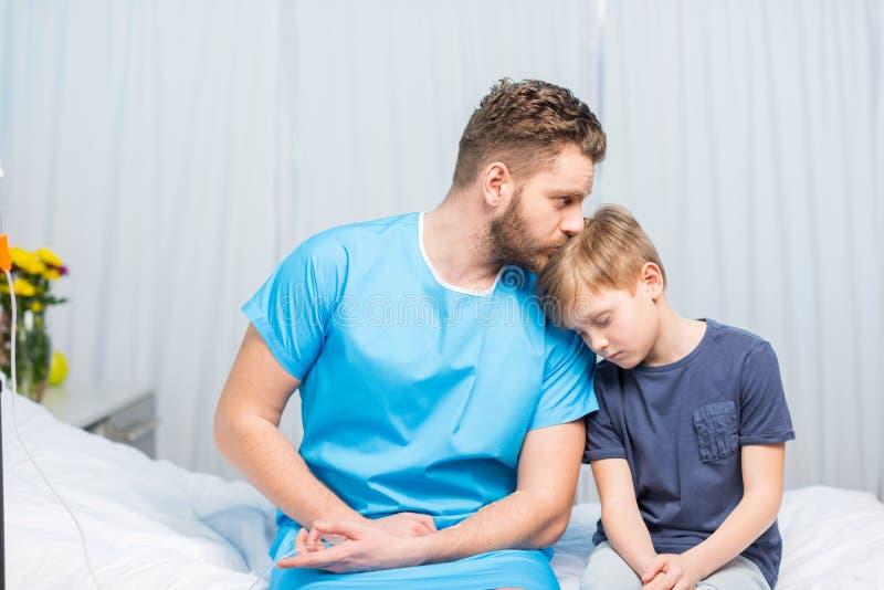 病的父亲和翻倒儿子一起坐医院病床 免版税图库摄影