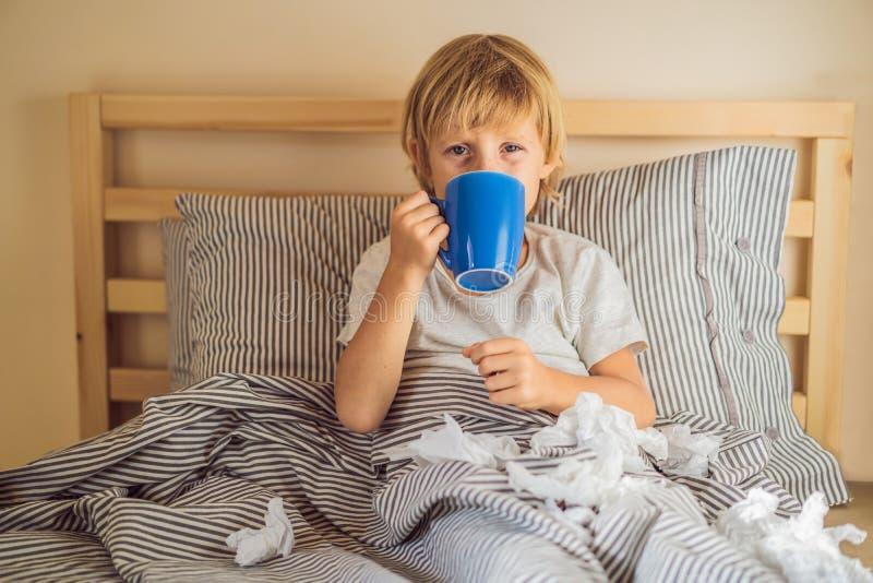 病的男孩饮用的茶在他的床上 病的孩子以热病和病症在床上 库存照片