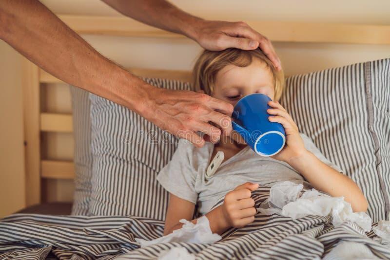 病的男孩饮用的茶在他的床上 病的孩子以热病和病症在床上 免版税库存图片