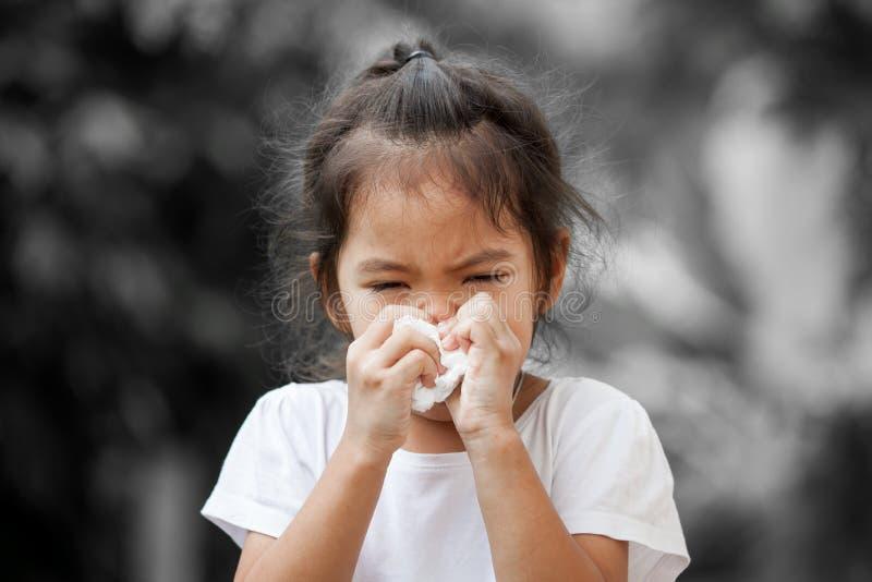 病的矮小的亚裔与组织的女孩抹的或清洗的鼻子 免版税库存照片