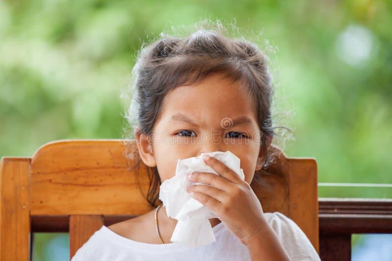 病的矮小的亚裔与组织的女孩抹的或清洗的鼻子 库存照片