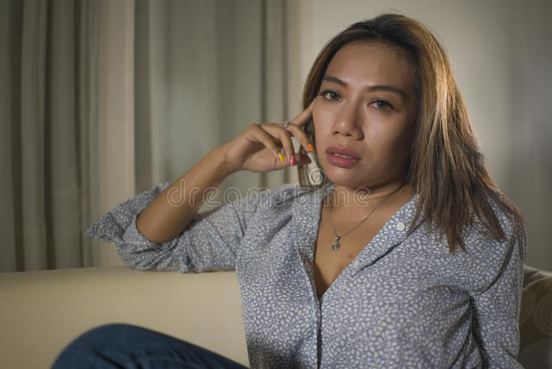 痛苦周道和迷茫的在家长沙发感觉伤心痛苦的年轻美丽的哀伤和沮丧的亚裔妇女 免版税库存照片