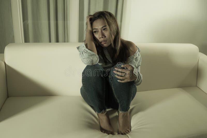 痛苦周道和迷茫的在家长沙发感觉伤心痛苦的年轻美丽的哀伤和沮丧的亚裔妇女 图库摄影