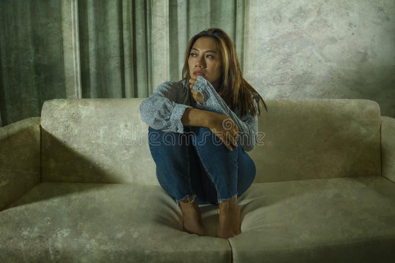 痛苦周道和迷茫的在家长沙发感觉伤心痛苦的年轻美丽的哀伤和沮丧的亚裔妇女 免版税库存图片