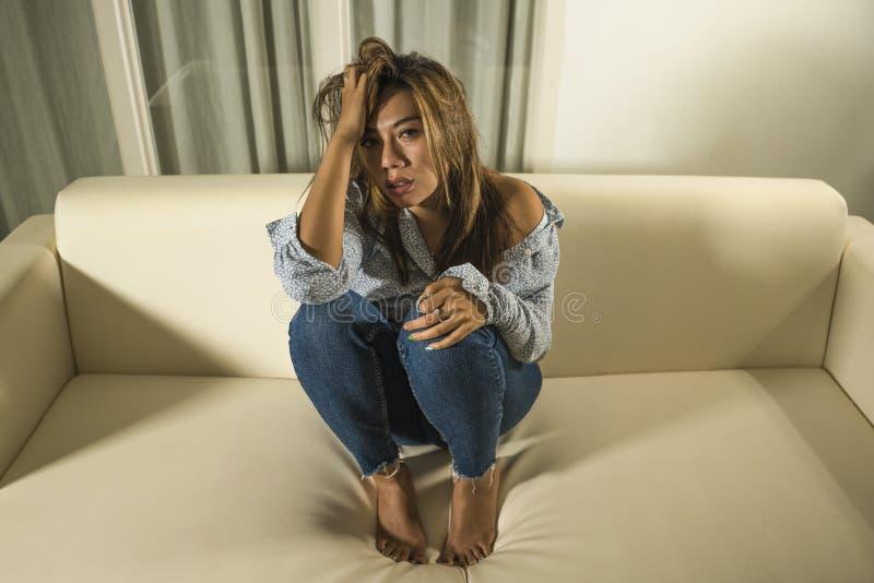 痛苦周道和迷茫的在家长沙发感觉伤心痛苦的年轻美丽的哀伤和沮丧的亚裔妇女 库存图片