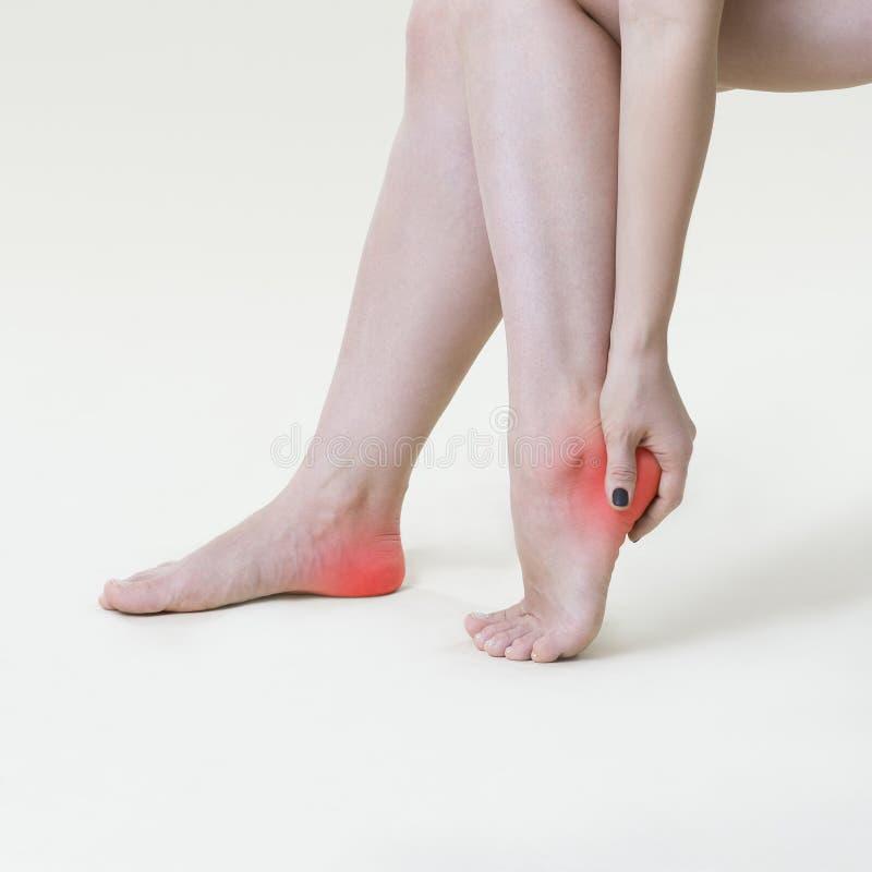 痛苦在妇女` s腿,女性脚按摩在米黄背景的 免版税库存图片