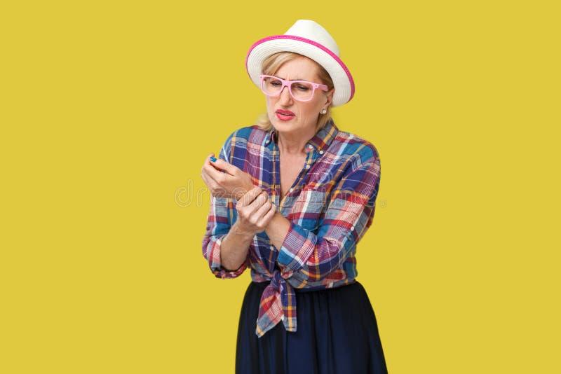 痛苦在手边或病的时髦的成熟妇女腕子画象便装样式的与站立和拿着她的帽子和镜片 库存图片