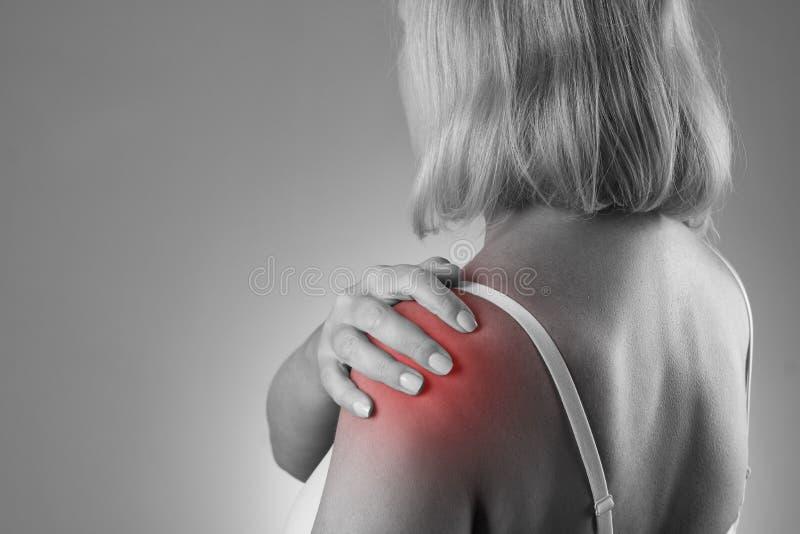 痛苦在肩膀,女性手关心,在妇女` s身体的疼痛 库存照片