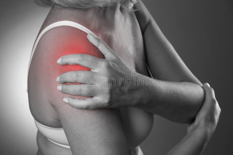痛苦在肩膀,女性手关心,在妇女` s身体的疼痛 免版税库存照片