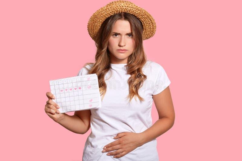 痛苦的期间概念 让烦恼的美丽的欧洲妇女有胃痉挛,感到不适,有月经,穿草帽和 免版税库存照片