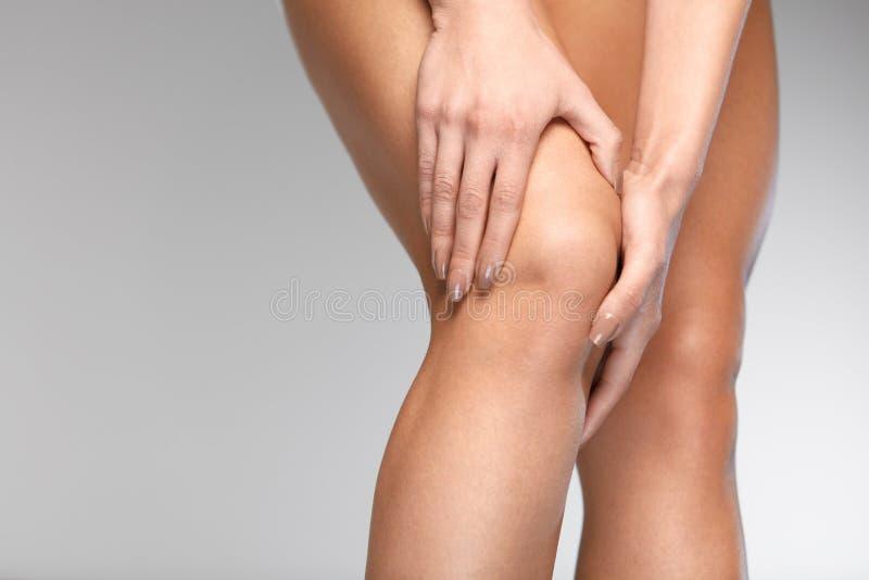 痛苦的膝盖 妇女在膝盖的感觉痛苦特写镜头  免版税库存照片