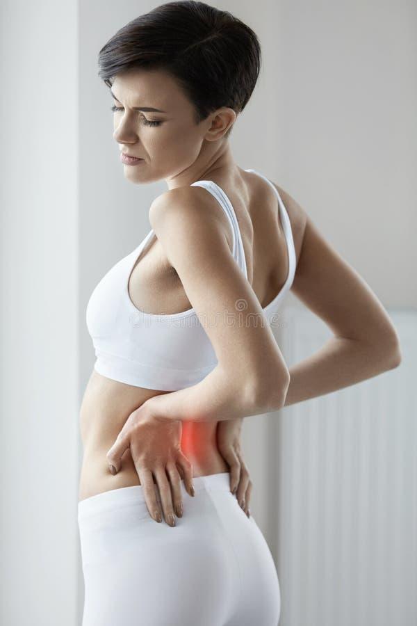 痛苦 有美丽的女性痛苦的感觉后面,腰疼 免版税库存照片
