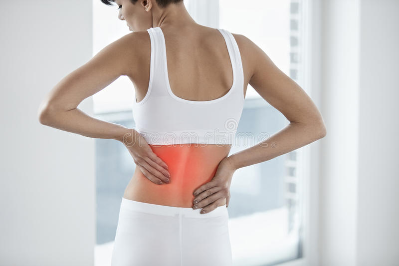 痛苦 有美丽的女性痛苦的感觉后面,腰疼 免版税库存图片