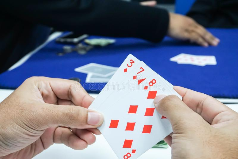 瘾概念-接近的人和啤牌卡片在赌博的手上 库存照片