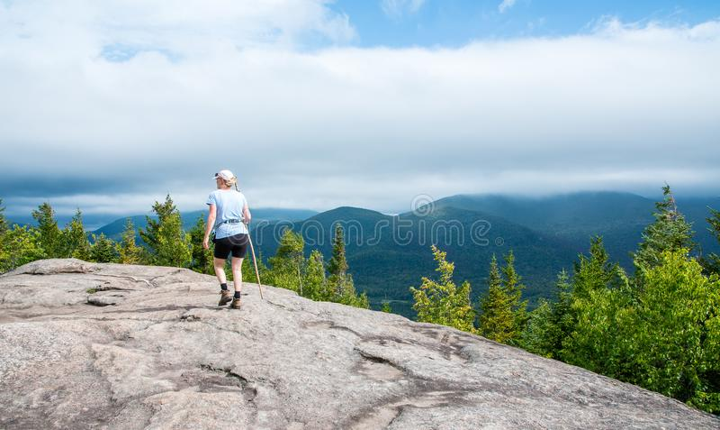 登上Jo普莱西德湖城山顶的女性远足者  免版税图库摄影