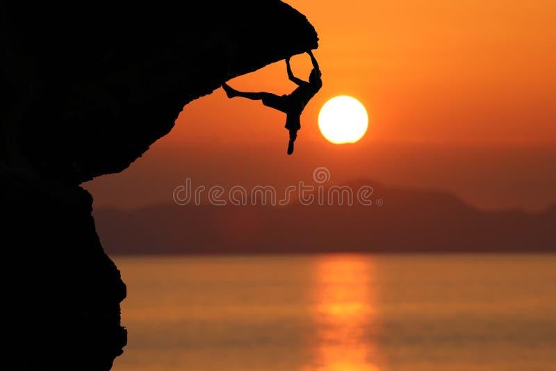 登山人剪影峭壁的反对美好的红色天空sunse 库存照片