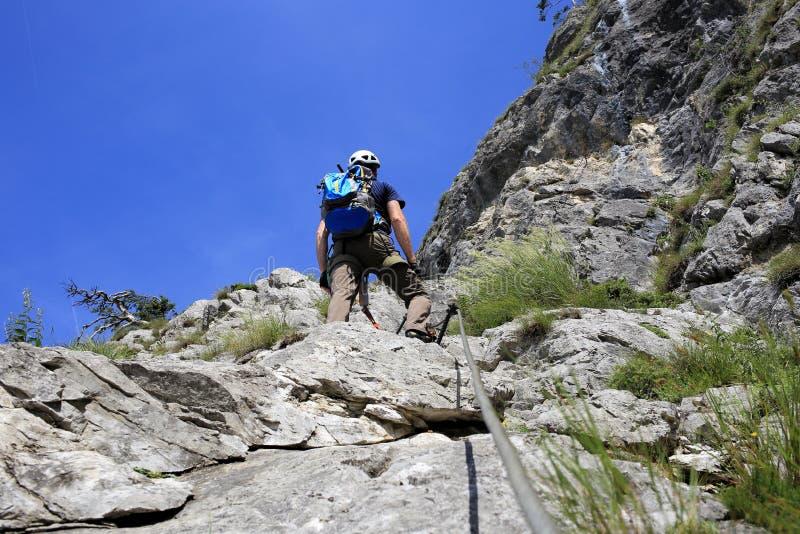 登山人在岩石墙壁上站立 免版税库存照片