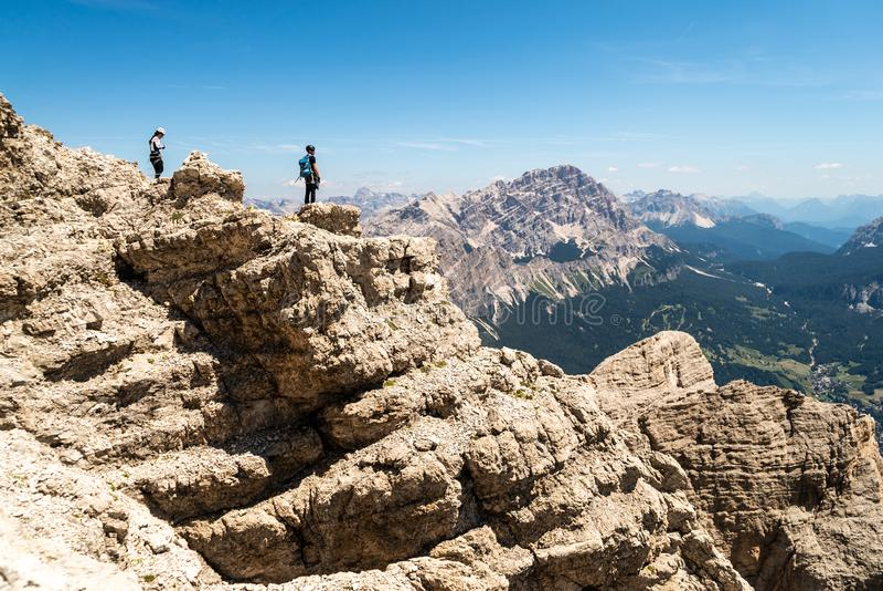 登山人在峭壁的剪影身分在白云岩 Tofana di Mezzo,蓬塔安娜,意大利 人庆祝成功在moun顶部 库存照片