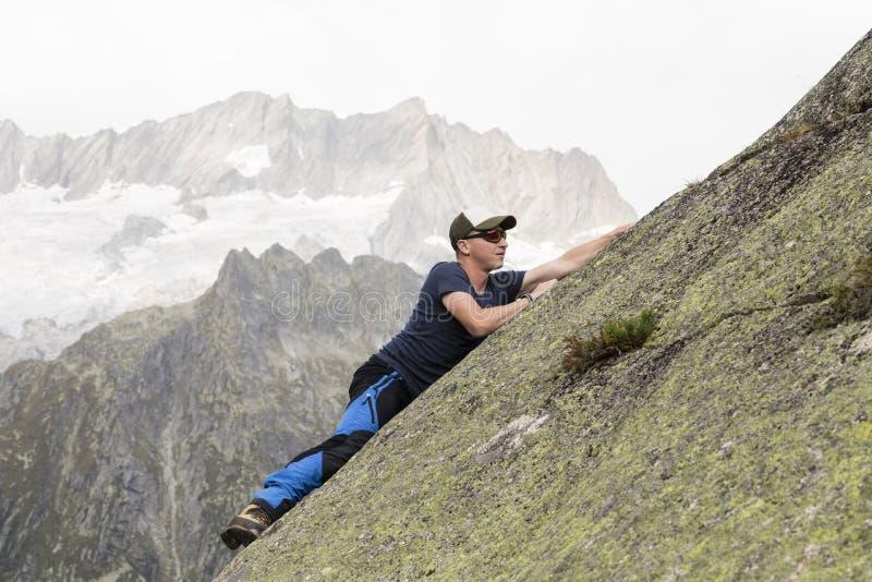 登山人在瑞士山的倾斜的岩石墙壁上上升 图库摄影