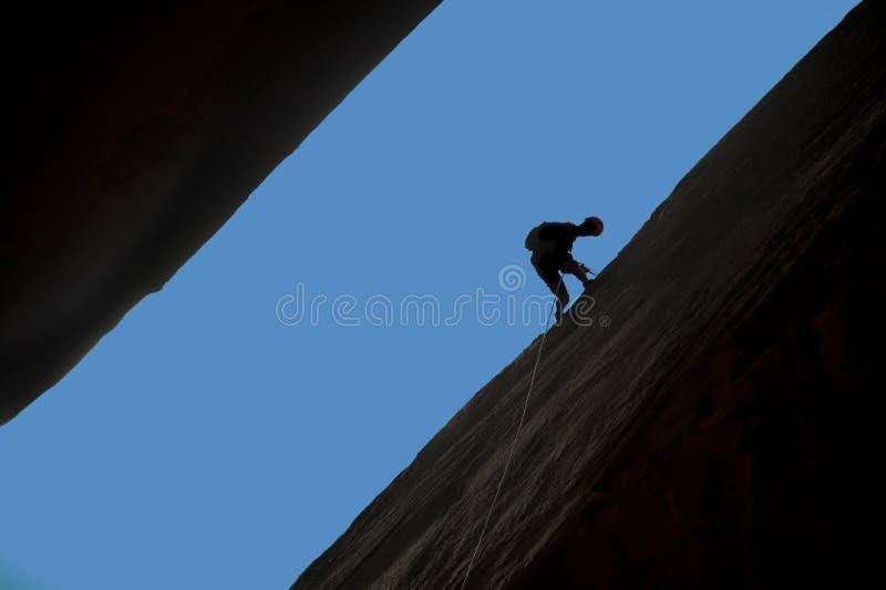 登山人坐式下降法的岩石剪影 库存照片