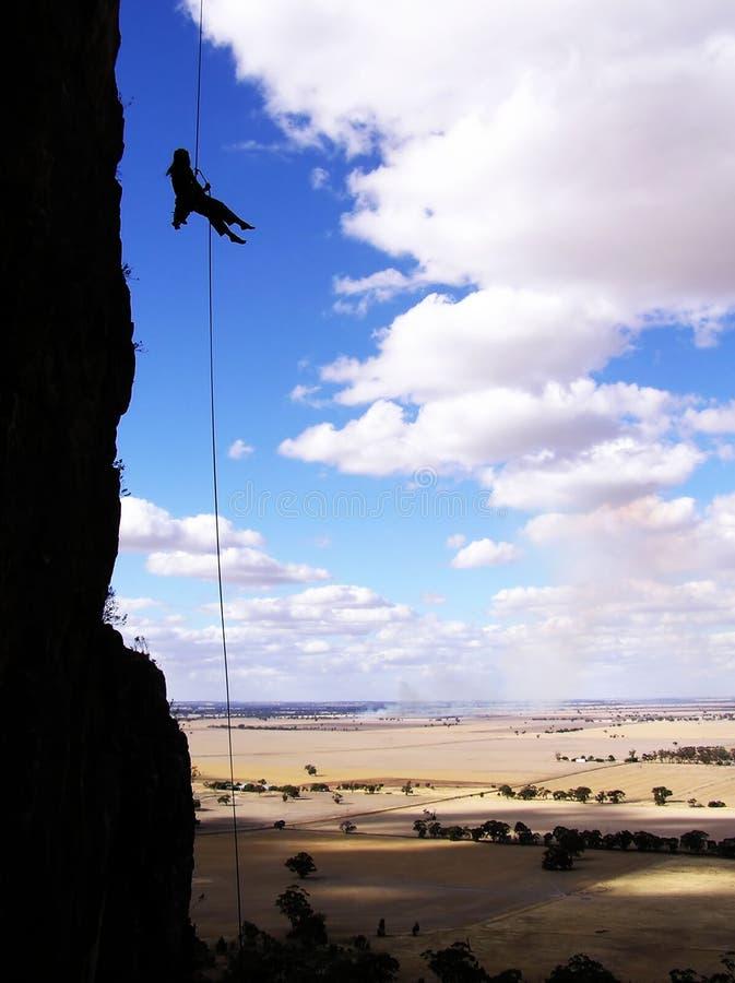 登山人坐式下降法的岩石 图库摄影