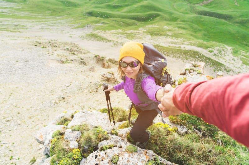 登山人帮助一名年轻登山家妇女到达山的上面 一个人给一个帮手妇女 视图 免版税库存图片